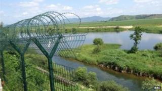 Razor wire delineates the border between North Korea and China