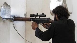 A Free Syrian Army fighter stands in a shooting position in Raqqa province, eastern Syria on 8 September 2013