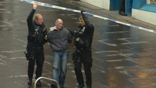 Russell Irvine being led away by police