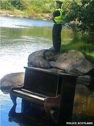 Officer Steve Band stands over the piano at the River Tay