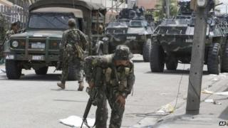 Government troopers, backed by armoured personnel carriers, position themselves at an intersection at the southern port city of Zamboanga in southern Philippines Wednesday, 11 September 2013