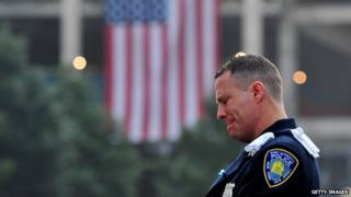 Daniel Henry, a Port Authority of New York/New Jersey police officer, pauses during a moment of silence at 9:01 am EDT, at the South reflecting pool of the 9/11 Memorial on 11 September 2013