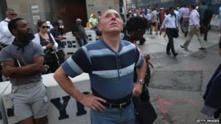 A man gazes at the One World Trade Center as church bells toll for 9/11 victims on 11 September 2013