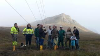 People at site of community wind turbine