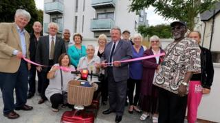 Bill Randall, chairman of the Housing Committee cutting the ribbon with other councillors, residents and tenant representatives