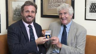Richard Madley, of auctioneers Dreweatts & Bloomsbury, and Welsh Sports Hall of Fame chairman Rhodri Morgan hold the medal