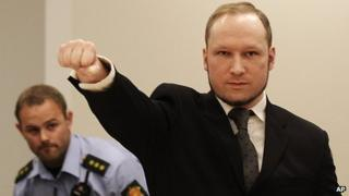 Anders Behring Breivik makes a salute after arriving in the court room at a courthouse in Oslo (24 August 2012)