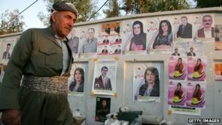 An Iraqi Kurdish man walks past electoral campaign posters in the northern Iraqi city of Irbil