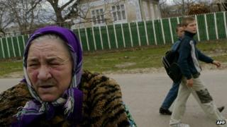 Children walk past an elderly woman in Moldova