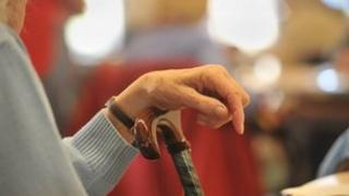 Pensioner rests hand on walking stick