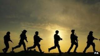 Soldiers running in a line, seen in silhouette