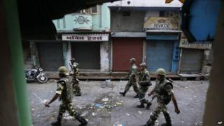 Indian army soldiers patrol during a curfew after deadly clashes between Hindus and Muslims in Muzaffarnagar on 9 Sept 2013