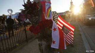 Flowers, flags and a child's drawing are pictured at a makeshift memorial outside the Navy Yard two days after a gunman killed 12 people before police shot him dead, in Washington, 18 September 2013