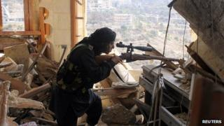 A Free Syrian Army fighter aims his weapon during a clash with government forces in Idlib, northwestern Syria.