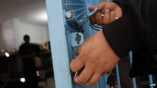 A prison guard closes the gate of a cell