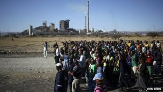 Miners chant slogans as they march past the Lonmin mine during the one-year anniversary commemorations to mark the killings of 34 striking miners by police (August 2013)