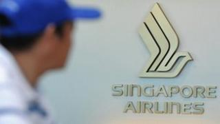 A man walks past a Singapore Airlines counter