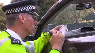 A police officer questions a driving instructor