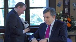 Damian McBride in the background as Gordon Brown gives an interview