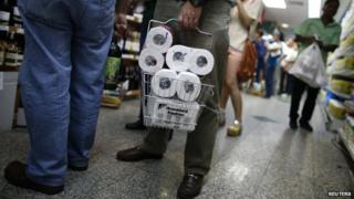 People wait in line as they buy toilet paper in a supermarket in Caracas 17 May, 2013.