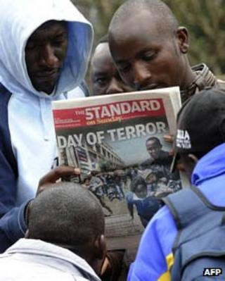 Kenyan men read newspaper
