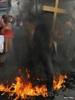 A Christian man in Lahore holding a cross jumps over burning tyres during a protest against a twin suicide bomb attack on a church in Peshawar, 22 September 2013