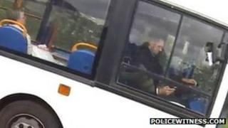 driver apparently using a mobile telephone while driving a bus