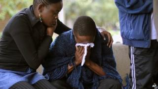 Stephen, centre, who lost his father in Saturday's attack at the Westgate Mall in Nairobi, Kenya, is comforted by relatives as he waits for the post-mortem exam at the city morgue Monday, Sept. 23, 2013.