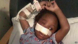 Rev Corey Brooks shows three-year-old Deonta Howard recovering from a gunshot wound at Mt Sinai Hospital in Chicago 23 September 2013