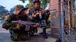 Kenyan soldiers take cover after heavy gunfire near Westgate mall in Nairobi on 23 September 2013