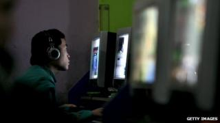 Young Chinese man in an internet cafe