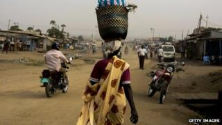 File image of a woman carrying goods in a basket on her head in South Sudan