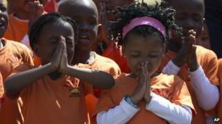 Schoolchildren pray for former South African President Nelson Mandela outside his home in Johannesburg, South Africa, Thursday, Sept. 5, 2013