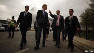 European Commission inspector, centre, walks with Gibraltar representatives