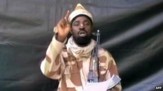 A grab taken from a video on 13 July 2013 shows the leader of the Islamist extremist group Boko Haram Abubakar Shekau dressed in camouflage and holding a Kalashnikov AK-47 rifle