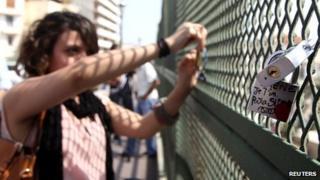 A woman locks a padlock onto the Telemly bridge on 7 September