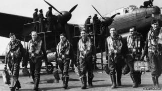 The crew of a Lancaster bomber walk away from their plane after a flight while ground crew check it over, April 1943
