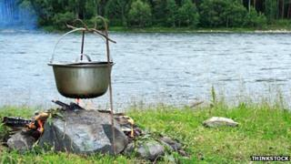 A pan hanging over a wood fire