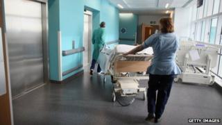Hospital staff and patient in corridor