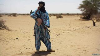 A fighter with the Tuareg separatist group MNLA (National Movement for the Liberation of Azawad) stands guard outside the local regional assembly, where members of the rebel group met with the Malian army, the UN mission in Mali and French army officers, in Kidal 23 June, 2013.
