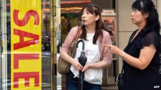 Shoppers outside a shop in Japan