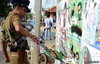 A policeman removes an election poster in Jaffna
