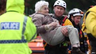 Volunteer Bryn Harrison helping an elderly woman in the floods in St Asaph in November 2012