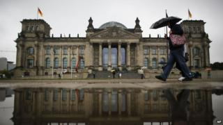 Two day's after Germany's national election tourists walk with umbrellas in front of the German parliament building, the Reichstag, in Berlin, Germany, Tuesday, 24 September, 2013.