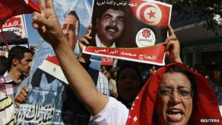 Protesters hold up a picture of murdered opposition leader Mohammed Brahmi during an anti-government demonstration in Tunisia.