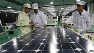 Workers inspect a solar panel in a Chinese factory