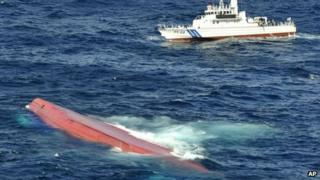 In this aerial photo, a capsized Japanese freighter Eifuku Maru No 18, foreground, as a Japan coast guard patrol boat conducts a search operation for missing crew members including the skipper and deputy skipper of the ship, off Izu Oshima, Japan, 27 September 2013