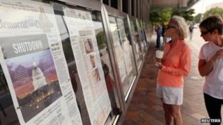women look at newspapers