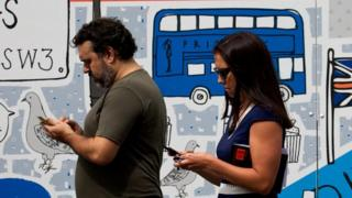 Man and woman holding phones