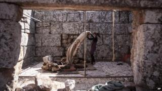A displaced Syrian girl walks upstairs from her family cave dwelling near Kafer Rouma, in ancient ruins used as temporary shelter by those families who have fled from the heavy fighting and shelling in Idlib province, on 27 September 2013